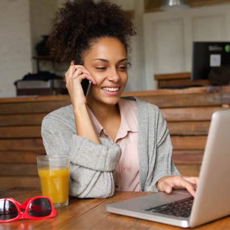 Young woman at computer on phone
